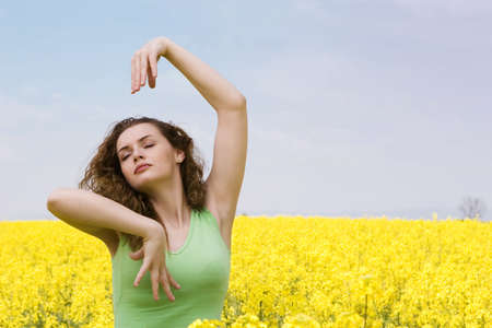 Portrait of a young woman doing yoga in rape field