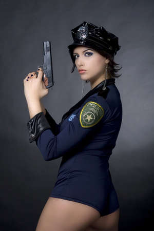 Sexy woman with police uniform in studio  on dark gradient background Stock Photo