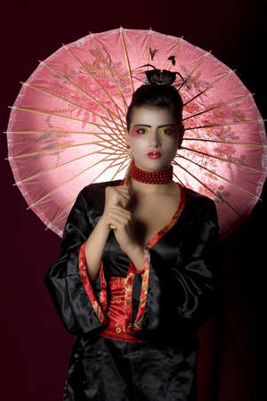 Sexy woman wearing geisha costume, holding an umbrella and looking at the camera. Studio shot photo