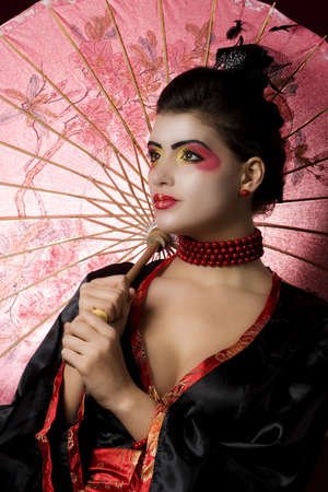 Geisha in studio with extreme makeup. Studio shot photo