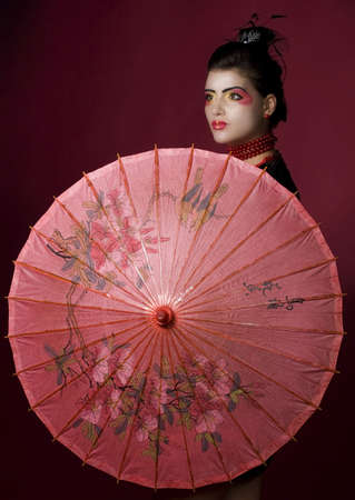 geisha holding a beautiful red umbrella. studio shot photo