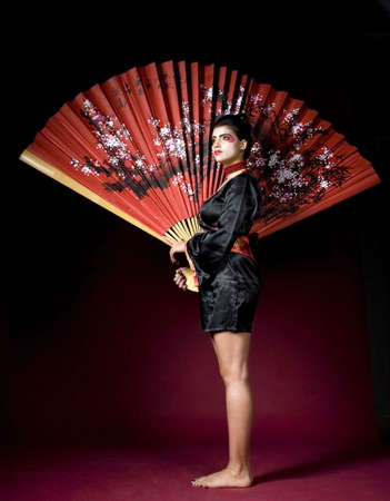 Full lenght portrait of a geisha with a big fan photo