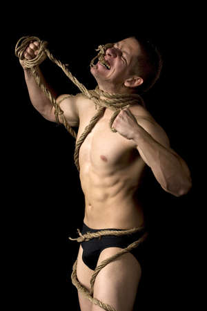 Studio image of a young man tied with ropes. Concept for freedom or escape