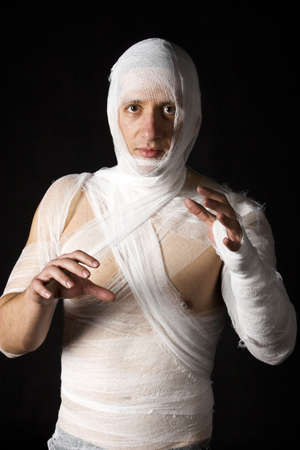 Studio image of a young man bandaged, on black background. Concept for health-care or ancient mummy