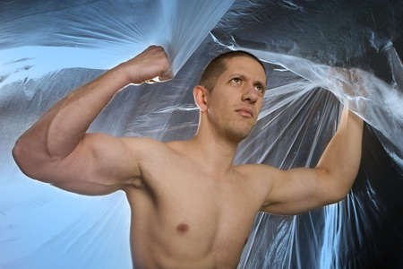 Studio image of a young muscular man on abstract blue background Stock Photo