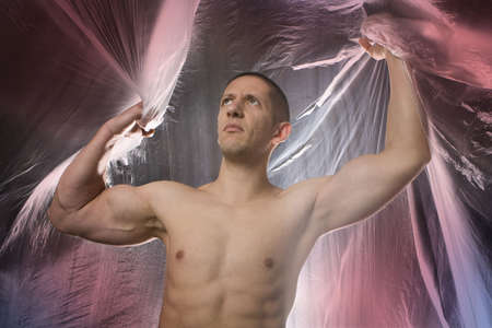 Studio image of a young muscular man on abstract colored background photo