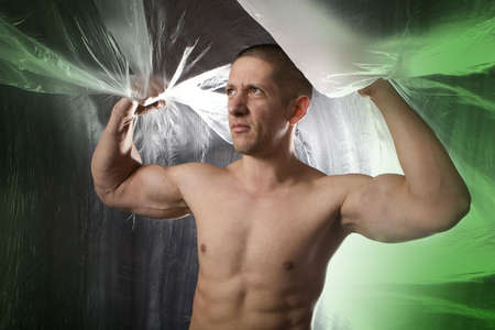 Studio image of a young muscular man on abstract green background