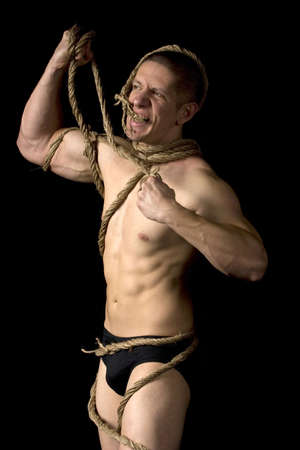 Studio image of a young man tied with ropes on black background. Concept for escape or freedom