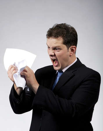 Frustrated businessman screaming and destroying documents.Studio shot