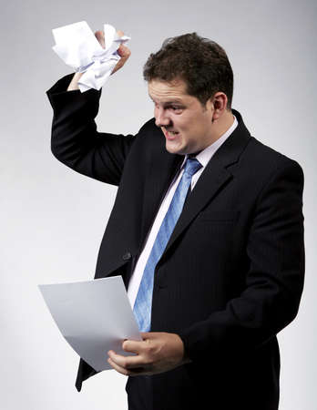 Angry businessman destroying a document. Studio shot