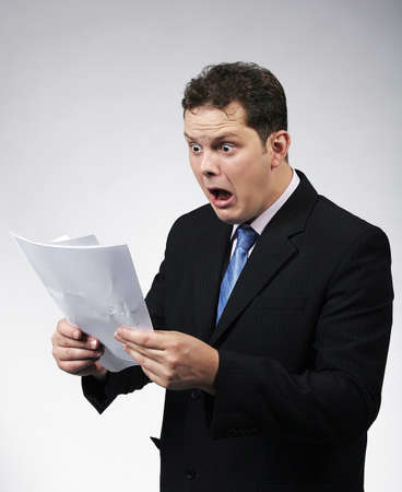 Shocked businessman looking at documents. Studio shots. Archivio Fotografico