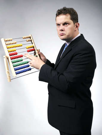 Confused businessman calculating with a multicolor abacus. Studio shot. Stock Photo