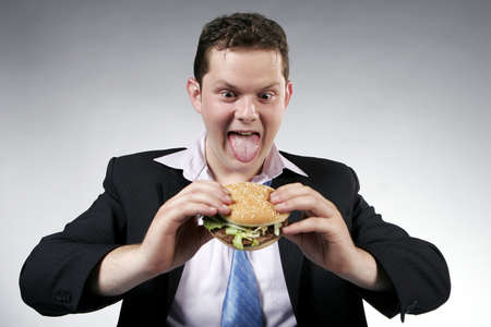 Businessman anxious to eat his hamburger. Studio shot