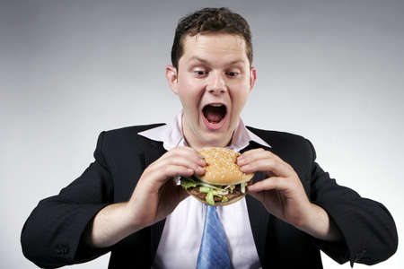 mouth opened: Businessman with mouth wide opened, ready to eat a burger