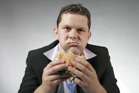 Disapointed businessman eating fast food burger