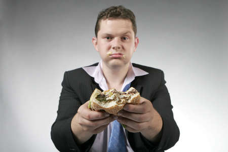 Unhappy businessman holding a hamburger. Focus is on the burger.