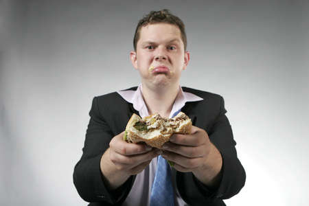 Unhappy businessman eating hamburger. Focus is on the burger