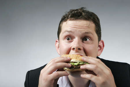 Hungry businessman enjoying a big hambruger for lunch. Studio shot