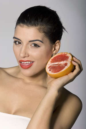 Portrait of a beautiful woman with grapefruit. Studio shots. Part of a series.