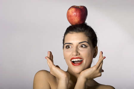 Part of photo series of a woman holding an apple on her head photo