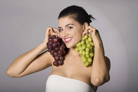 Part of photo series. Woman with mix of grapes. Studio shot