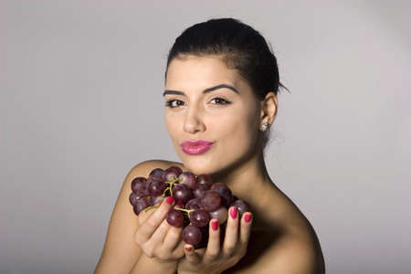 Part of photo series . Woman with red grapes. Studio shots photo
