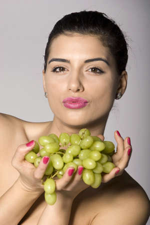 Part of photo series of a woman enjoying fresh green grapes. Studio shot