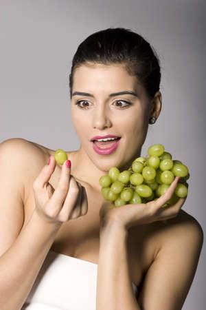 Part of photo series of a woman enjoying fresh green grapes. Studio shot photo