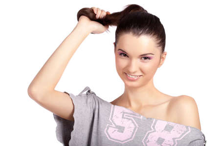 Beautiful young woman pulling her hair gently and smiling at the camera. High resolution image taken in studio. Isolated on pure white background with copy space for your ad.