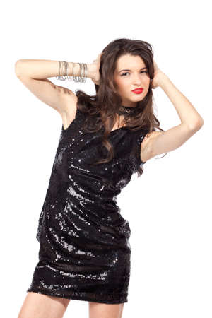 Attractive young woman posing in sequin dress, with alluring smile and looking at camera. Studio image, isolated on white background.