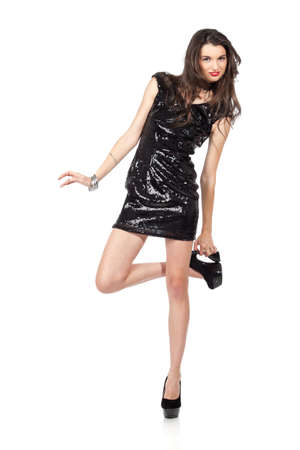 girls night out: Attractive young woman posing in sequin dress, with alluring smile and looking at camera, playing with shoes. Studio image, isolated on white background. Stock Photo