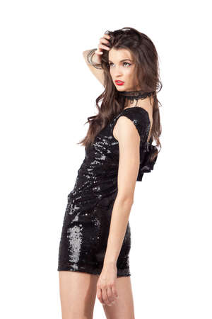 Attractive young woman posing in sequin dress, looking away. Studio image, isolated on white background. Stock Photo - 12024047
