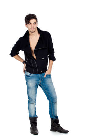 Handsome young fashion model standing and wearing jeans, boots and a black jacket. Isolated on white background. Studio vertical image. photo