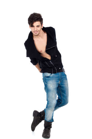 Handsome happy young fashion model posing wearing jeans, boots and a black jacket. Isolated on white background. Studio vertical image. Stock Photo