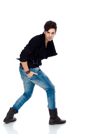 Handsome young fashion model wearing jeans, boots and a black jacket. Isolated on white background. Studio vertical image. photo