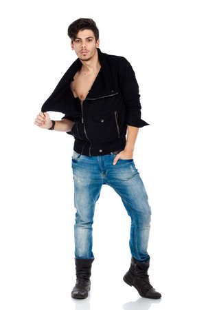 Sexy young fashion model wearing jeans, boots and a black jacket. Isolated on white background. Studio vertical image. photo