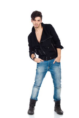 Attractive young fashion model wearing jeans, boots and a black jacket. Isolated on white background. Studio vertical image. photo