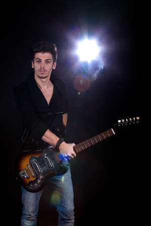 Concept for rock concert. Artistic image of young cool man  playing electric guitar. Image taken in studio with backlight and lens flare. Stock Photo - 12388988
