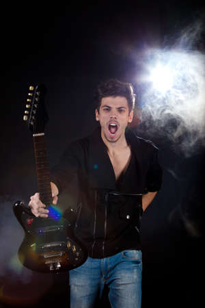 Concept for rock concert. Artistic image of young cool man  playing electric guitar. Image taken in studio with backlight and lens flare. photo