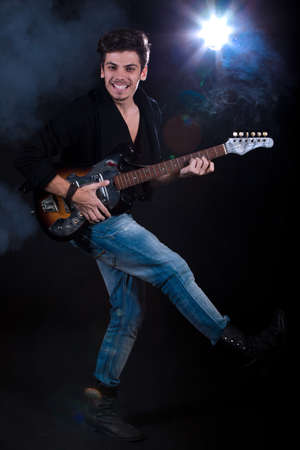 Concept for rock concert. Artistic image of young cool man  playing electric guitar. Image taken in studio with backlight and lens flare. Stock Photo - 12388993
