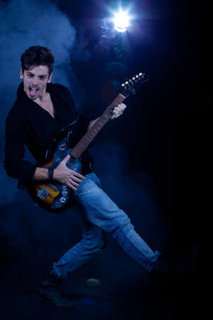 Concept for rock concert. Artistic image of young cool man  playing electric guitar. Image taken in studio with backlight and lens flare. Stock Photo - 12388952