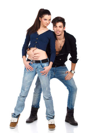 Young couple of two attractive happy fashion models wearing jeans looking at camera. Isolated on white background. High resolution studio image Stock Photo - 12389036