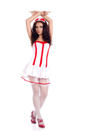 Sexy young nurse with long curly hair and hands crossed above her head on isolated white background. High resolution studio image with copy space for text. photo