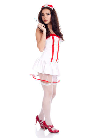 Sexy young nurse with long curly hair wearing red high heels shoes and holding a syringe  on isolated white background. High resolution studio image with copy space for text. Stock Photo