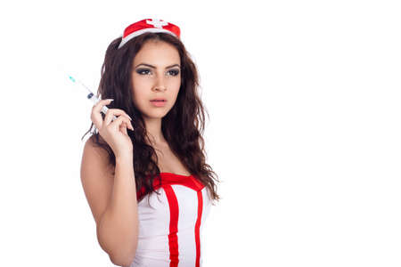 Portrait of a sexy young nurse with long curly hair holding a syringe on isolated white background. High resolution studio image with copy space for text. photo