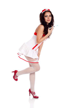 Full body shot of a sexy beautiful young nurse wearing red high heels shoes holding a syringe on isolated white background. High resolution studio image with copy space for text. photo