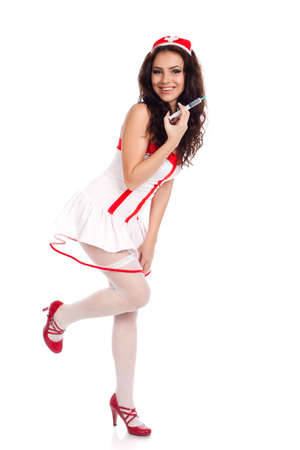Full body shot of a sexy beautiful young nurse wearing red high heels shoes holding a syringe  and smiling on isolated white background. High resolution studio image with copy space for text. photo