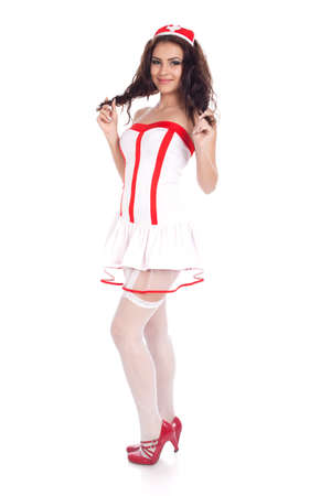 Full body shot of a sexy beautiful young nurse wearing red high heels shoes playing with her hair and smiling on isolated white background. High resolution studio image with copy space for text. photo