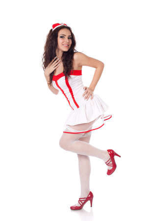 Full body shot of a sexy beautiful young nurse wearing red high heels shoes touching herself and smiling on isolated white background. High resolution studio image with copy space for text. photo
