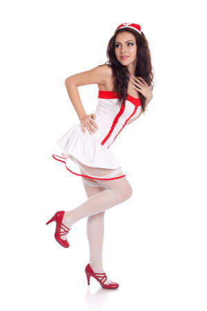 Full body shot of a sexy beautiful young nurse wearing red high heels shoes looking aside on isolated white background. High resolution studio image with copy space for text. photo
